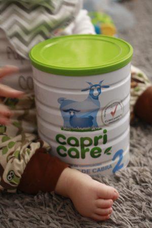bebé sentada con la lata de leche capri care 2 entre las piernas