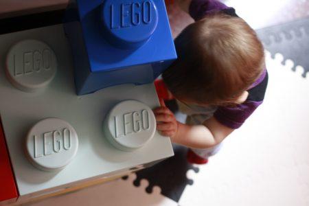 Elorac con 8 meses subida de pie apoyada en unos cubos de LEGO