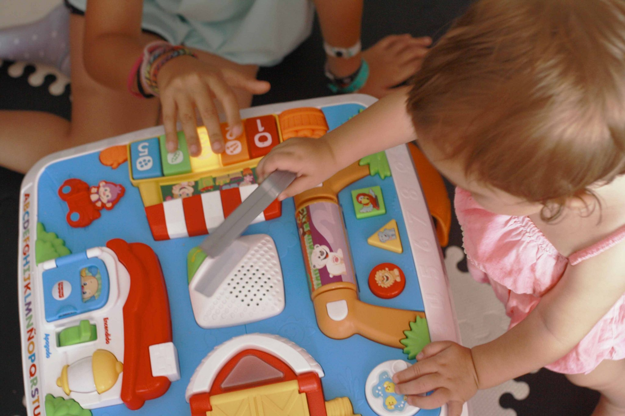 bebé y su hermana mayor (1 y 6 años) jugando con la mesa de actividades de fisher price
