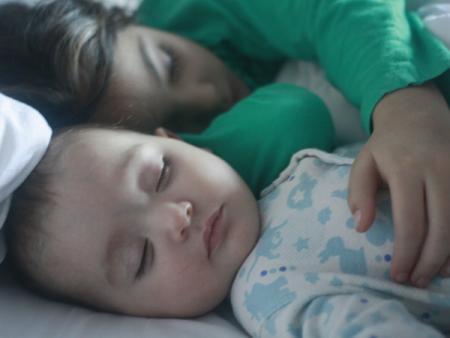 La dos hermanas durmiendo, la mayor de cinco años le tiende el brazo por encima y abraza a su hermana bebé
