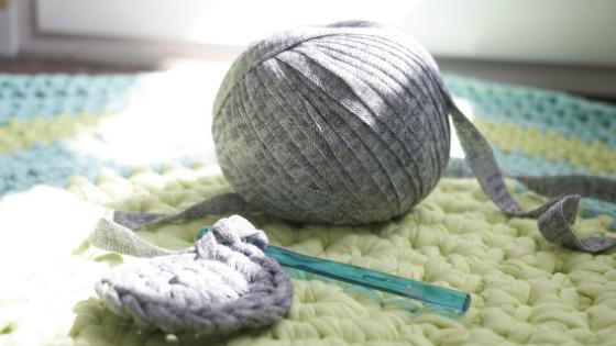 Bobina de trapillo ligero gris encima de una alfombra de trapillo